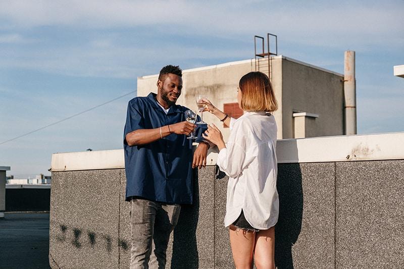 Ein Mann und eine Frau rösten mit einem Glas Wein auf dem Dach des Gebäudes