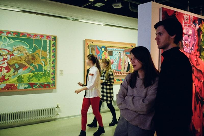 Ein Mann und eine Frau schauen sich eine Kunstausstellung in der Galerie an