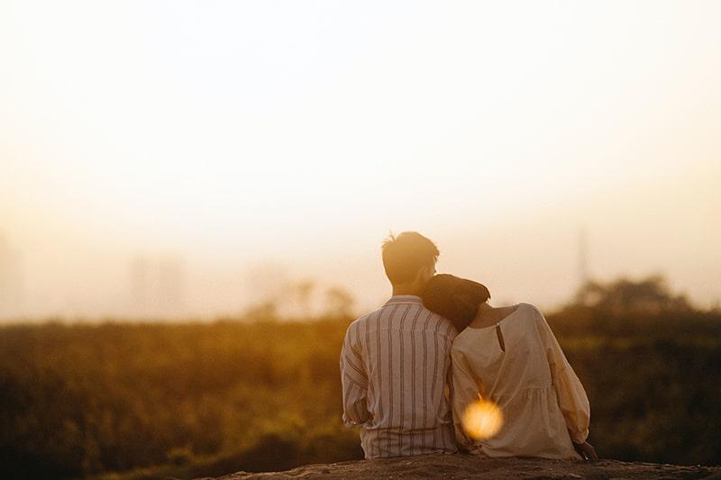 Ein Mann und eine Frau sitzen auf dem Boden und stützen sich aufeinander, während sie den Sonnenuntergang beobachten