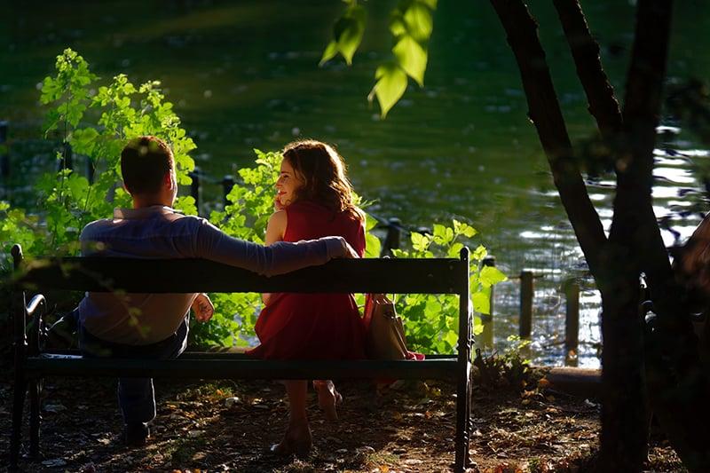 Ein Mann und eine Frau sitzen auf der Bank in der Nähe des Sees bei einem Date