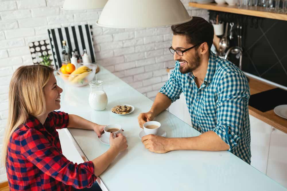 Ein Mann und eine Frau sitzen sich beim Kaffee gegenüber und lachen