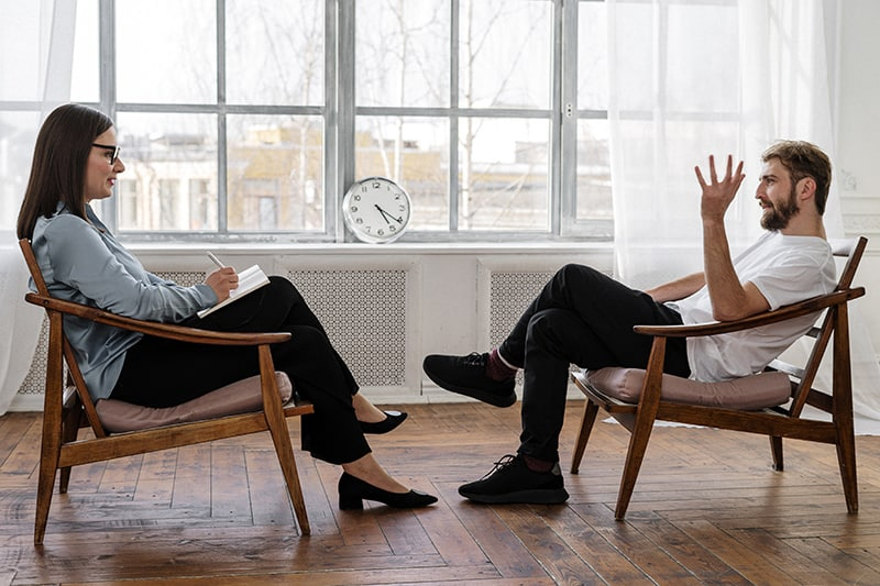 Ein Mann und eine Frau unterhalten sich, während sie sich im Sessel gegenüber sitzen