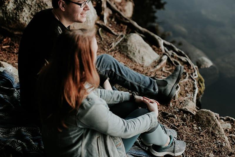 Ein Mann und eine Frau unterhalten sich neben dem Fluss und sitzen auf dem Boden
