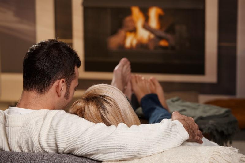 Ein Paar genießt es auf dem Sofa am Feuer, das im Kamin brennt
