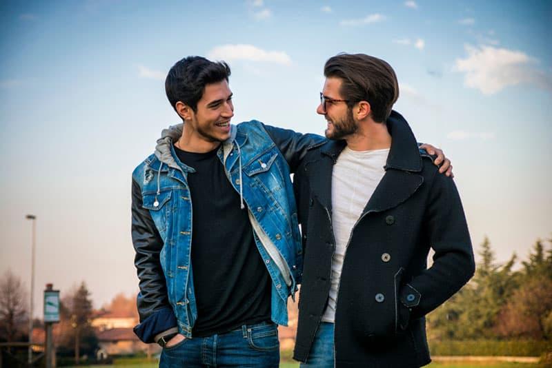 zwei beste Freunde gehen in Umarmung und reden