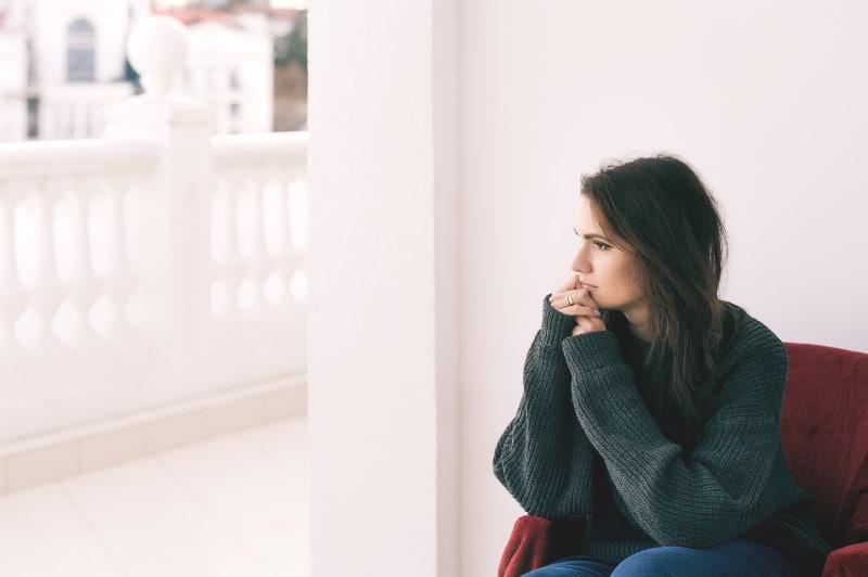Ein besorgtes Mädchen sitzt auf dem Balkon