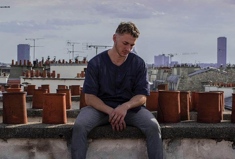 Ein einsamer Mann sitzt auf der Dachterrasse und schaut nach unten