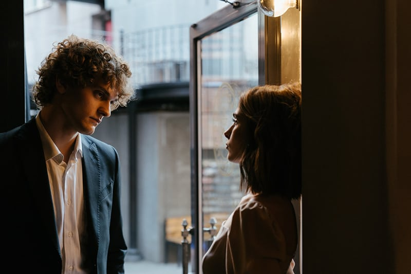 Ein ernster Mann steht einer Frau gegenüber, die sich an die Tür lehnt