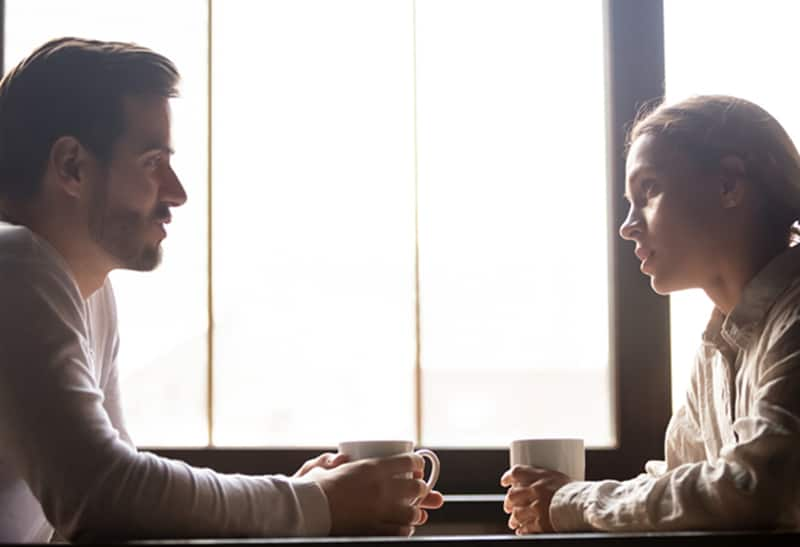 Ein ernster Mann und eine Frau unterhalten sich, während sie am Tisch sitzen