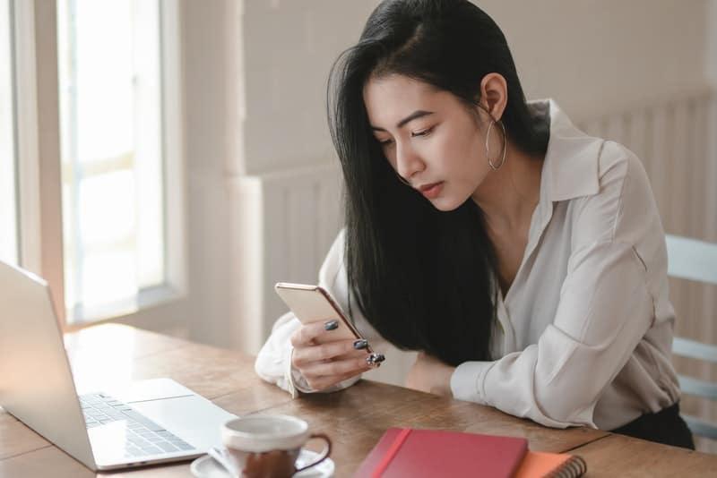 Ein ernstes chinesisches Mädchen sitzt an ihrem Schreibtisch und tippt auf SMS