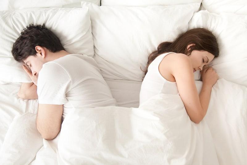 Ein gleichgültiger Mann und eine gleichgültige Frau, die getrennt hintereinander im Bett schlafen und Beziehungsprobleme haben