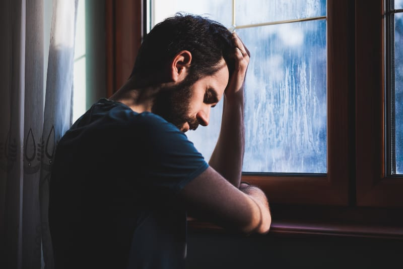Ein junger trauriger Mann steht am Fenster