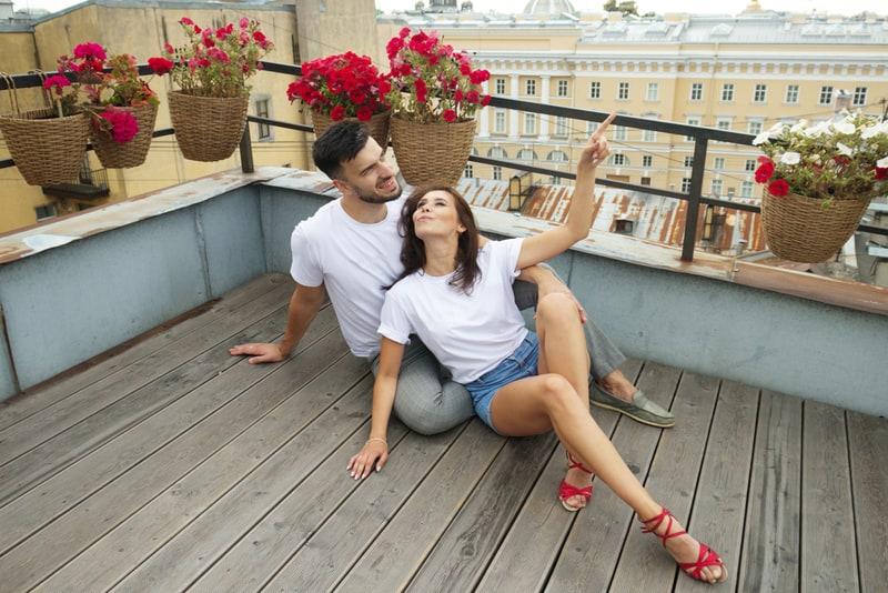Ein junges lächelndes Liebespaar sitzt auf der Terrasse