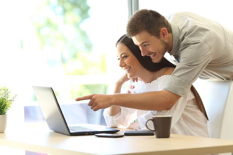 Ein lächelnder Mann, der hinter seiner Freundin steht und am Tisch vor dem Computer sitzt