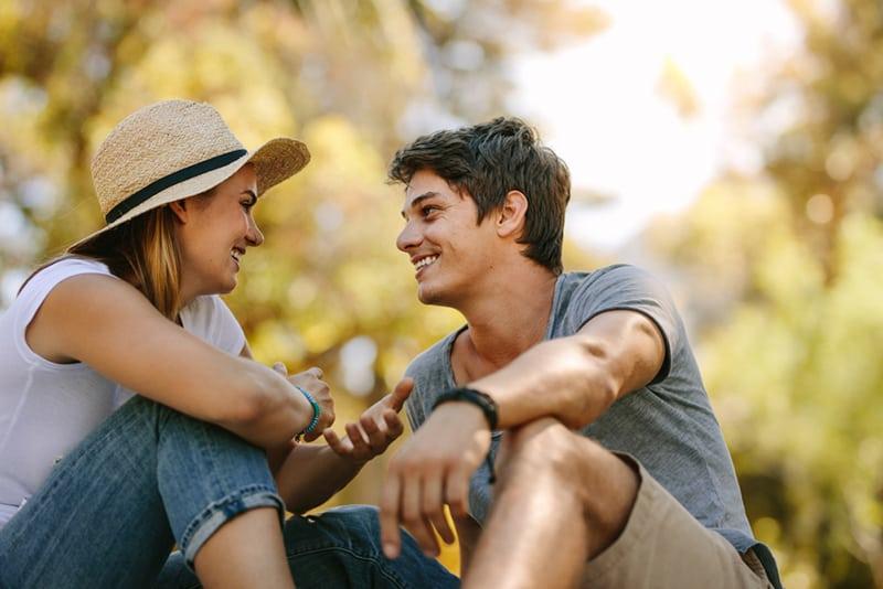 Ein lächelnder Mann und eine Frau sprechen miteinander, während sie im Park sitzen