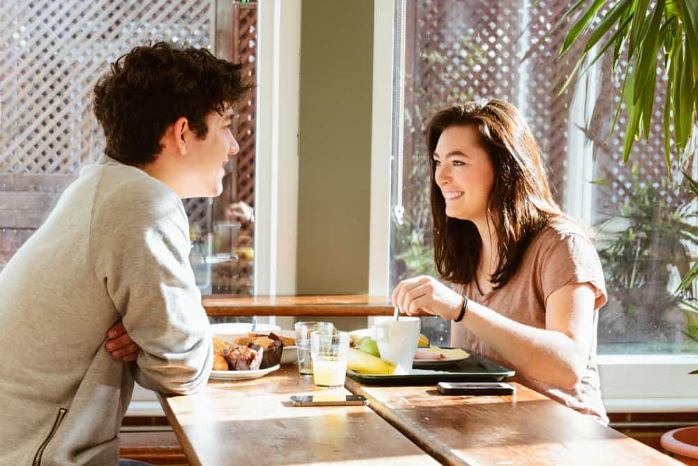 Ein lächelnder Mann und eine lächelnde Frau unterhalten sich beim Frühstück