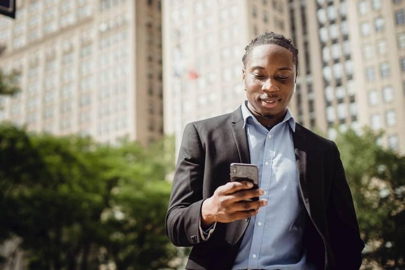 Ein lächelnder schwarzer Mann steht draußen und benutzt ein Smartphone