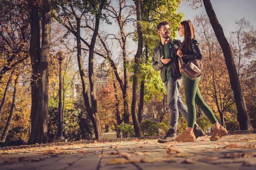 Ein liebevolles Paar geht durch den Park und sie reden