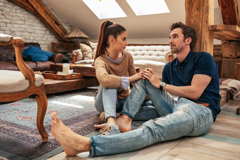 Ein liebevolles Paar sitzt auf dem Boden im Zimmer und hält beim Reden die Hände