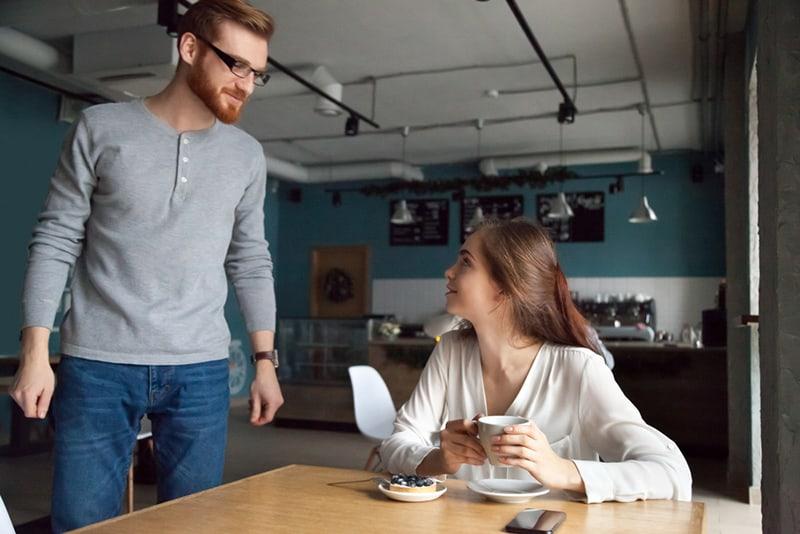 Ein nervöser Mann steht neben einer Frau, die im Café am Tisch sitzt