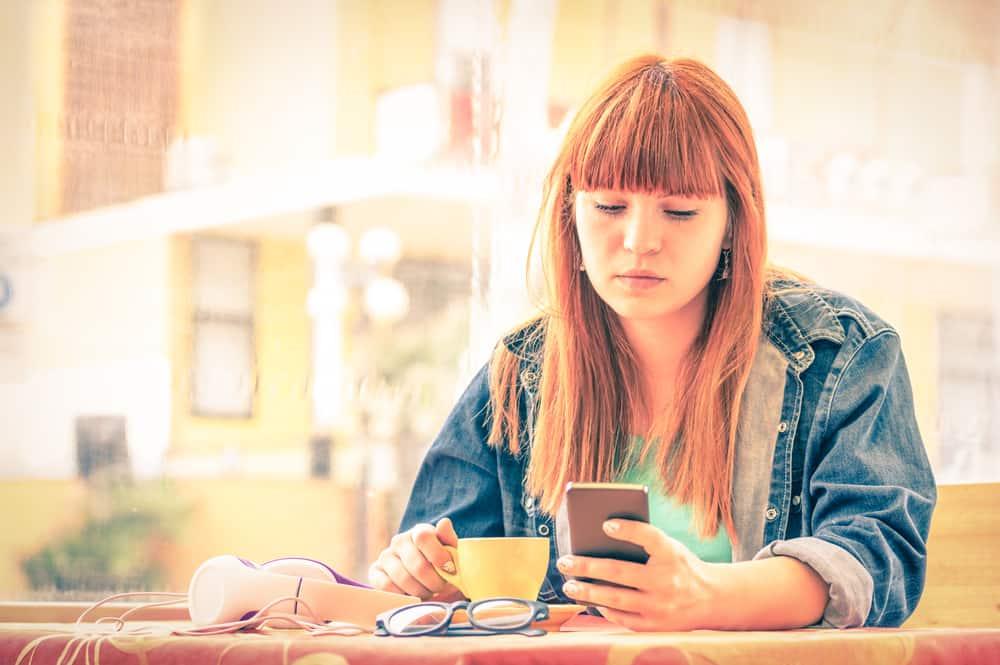 Ein rothaariges Mädchen sitzt in einem Café und benutzt ein Handy