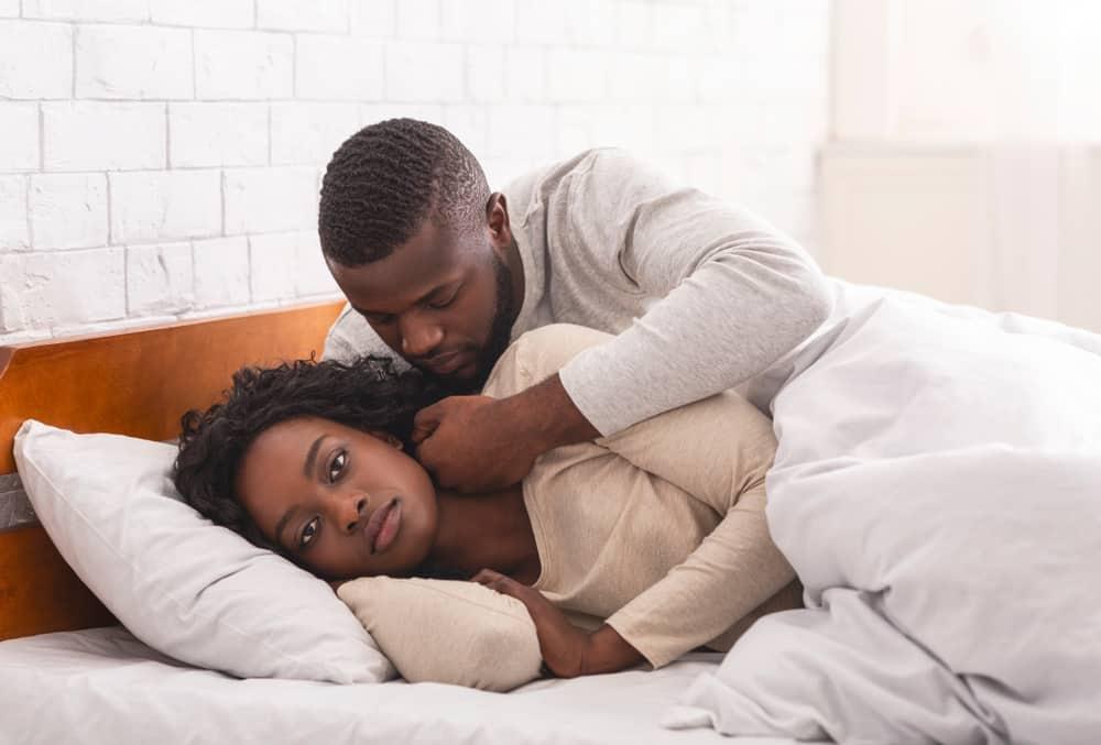 Ein schwarzer Mann in einem Schlafzimmerbett streichelt das Gesicht einer wütenden Frau