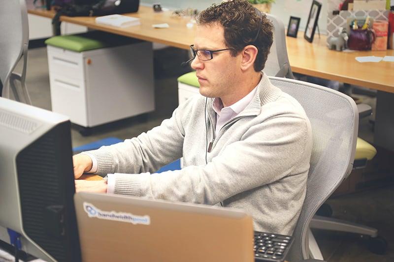 Ein stressiger Mann, der im Büro vor dem Computer arbeitet