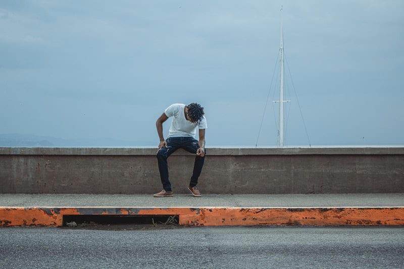 Ein trauriger Mann sitzt auf dem Bürgersteig neben der Straße