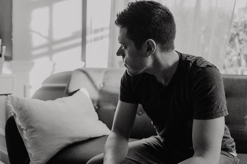 Ein trauriger Mann sitzt auf der Couch und schaut zur Seite