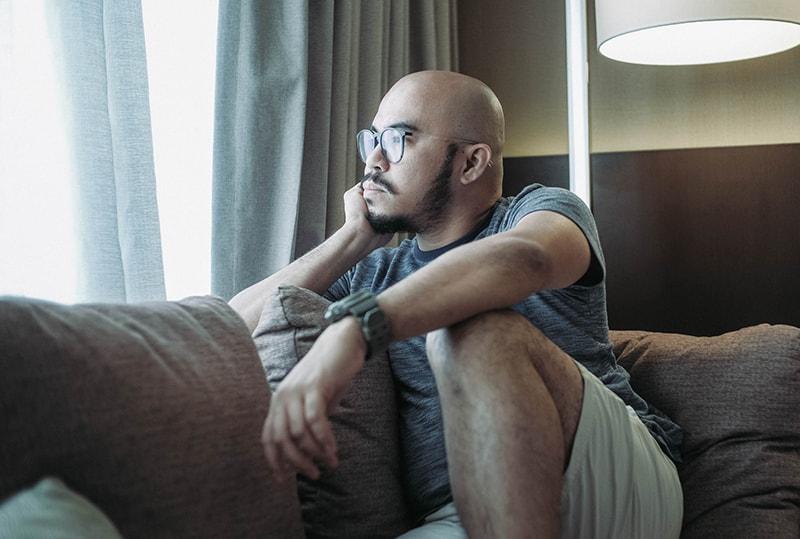 Ein trauriger Mann sitzt auf der Couch und schaut durch das Fenster