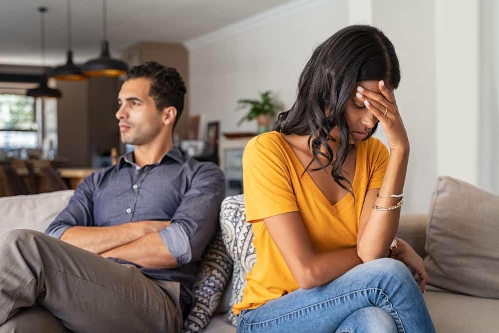 Ein trauriges Liebespaar sitzt nach einem Streit auf der Couch