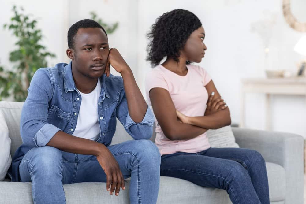 Ein trauriges Paar sitzt nach einem Streit auf einem Zweisitzer