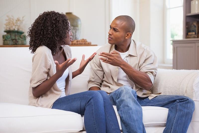 Ein verärgerter Ehemann spricht mit einer Frau, die verwirrt aussieht, während sie auf der Couch sitzt