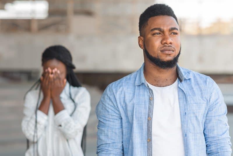 Ein wütender schwarzer Mann hinterlässt eine traurige Frau