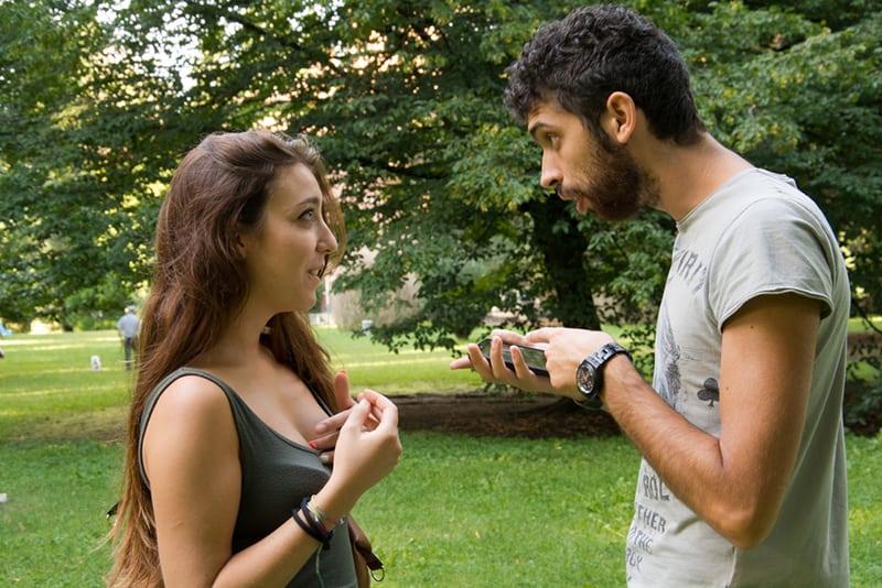 Ein zweifelhafter Mann bat seine Freundin um eine Erklärung, während er auf das Smartphone zeigte