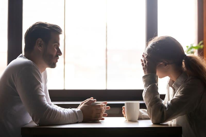 Eine Frau berührt ihre Stirn, während ein Mann im Café mit ihr spricht