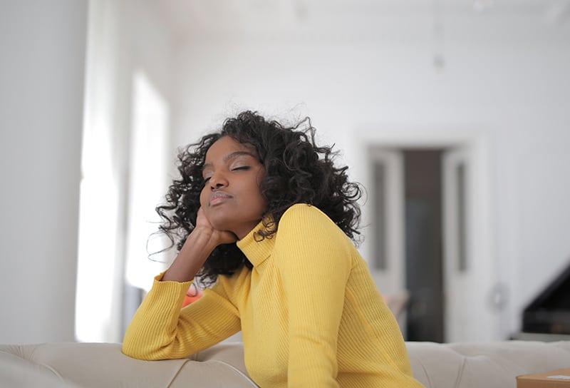Eine Frau in einem gelben Pullover schloss die Augen, während sie sich auf der Couch entspannte