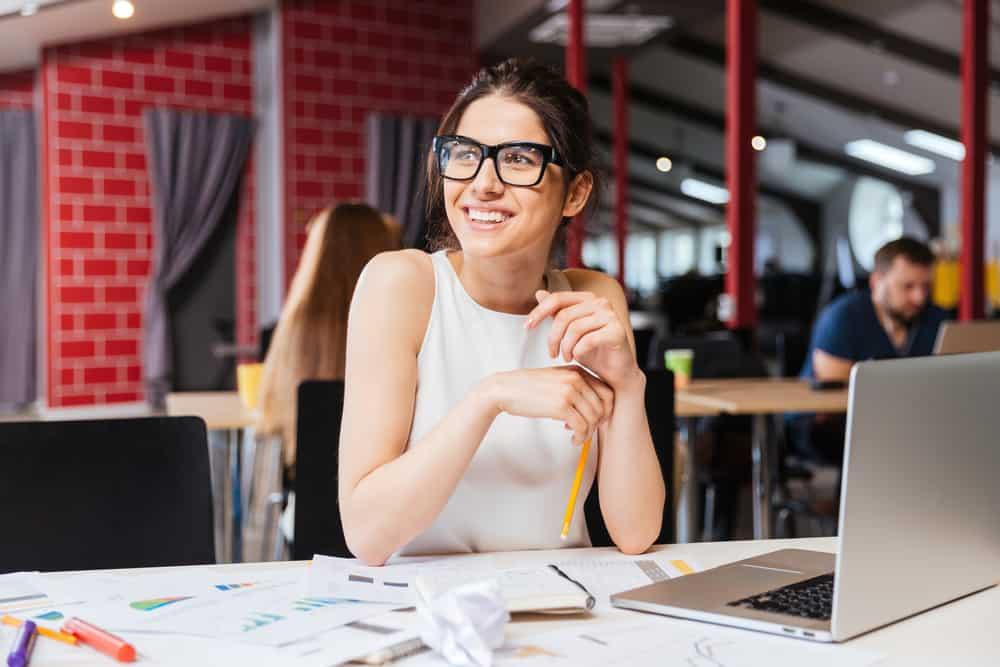 Eine Frau mit Brille sitzt hinter einem Laptop und lacht