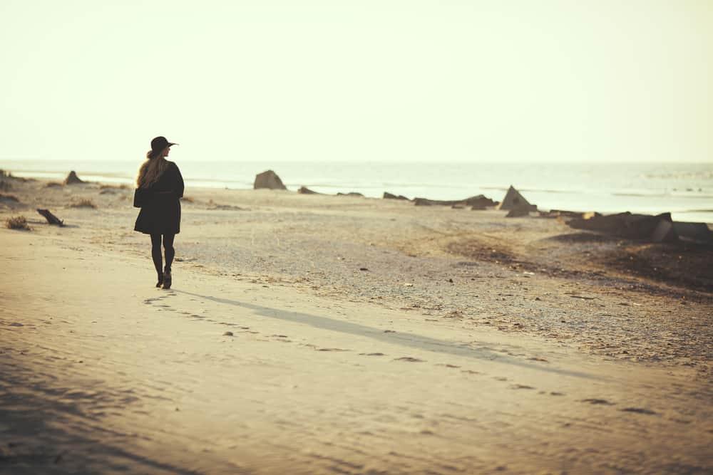 Eine Frau mit Mantel setzt den Strand