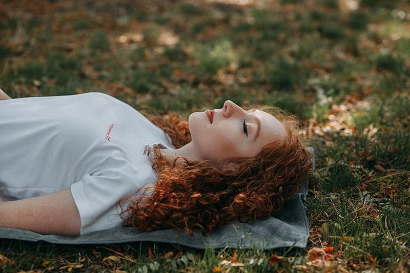 Eine Frau mit geschlossenen Augen lag auf der grauen Matte im Park