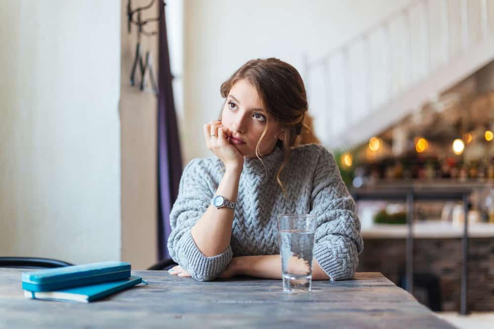 Eine Frau sitzt in einem Café und langweilt sich