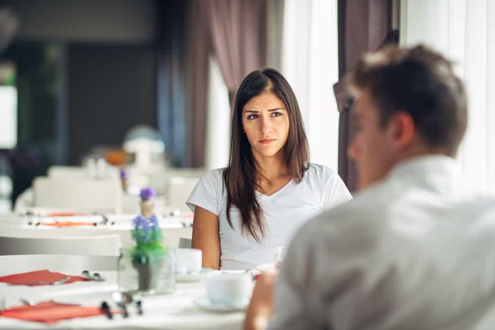 Eine Frau sitzt mit einem Mann in einem Restaurant und denkt nach