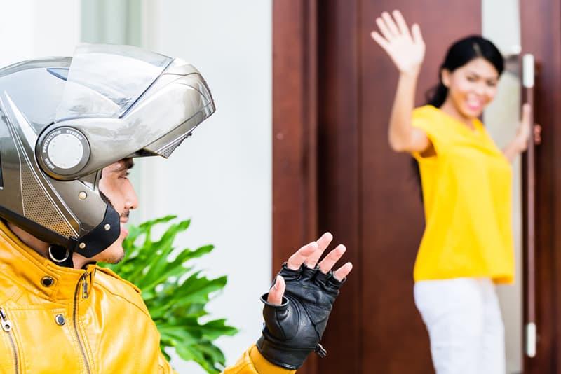 Eine Frau, die an der Tür steht und ihrem Freund mit Helm winkt