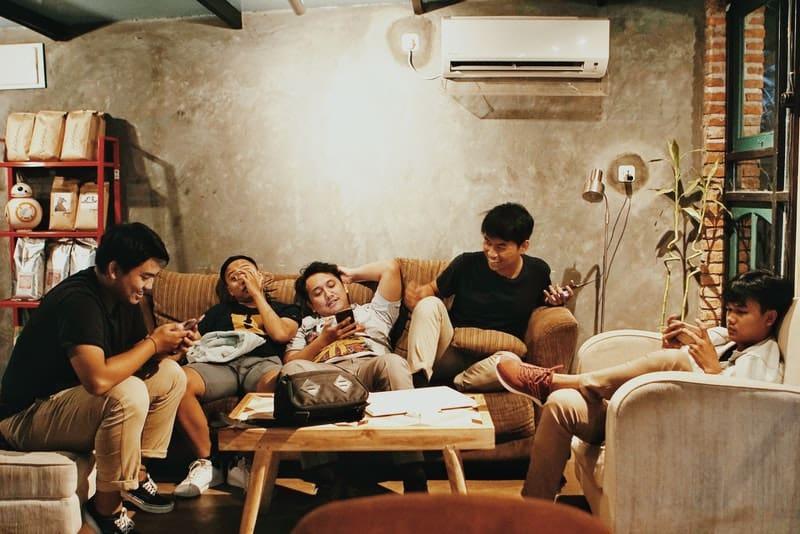 Eine Gruppe von Freunden hängt in einem Wohnzimmer ab
