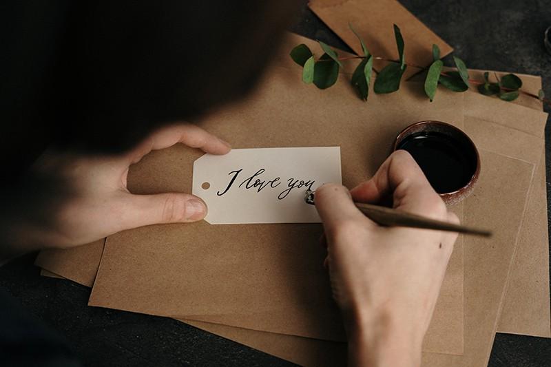 Eine Person, die schreibt, ich liebe dich auf einem Papier in englischer Sprache