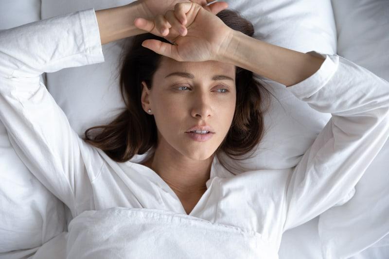 Eine depressive Frau liegt im Bett
