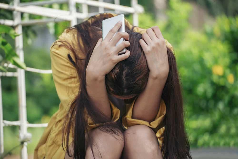 Eine depressive Frau mit einem Handy in der Hand sitzt zusammengerollt auf der Treppe