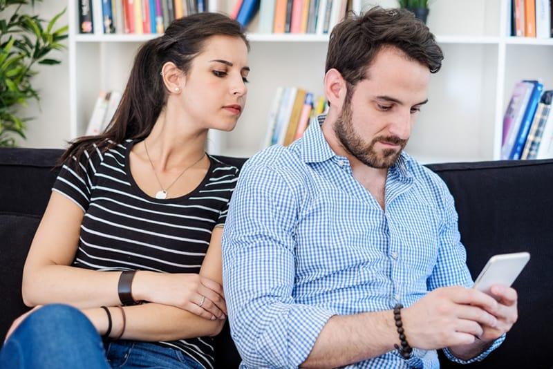 Eine eifersüchtige Frau, die einen Freund ausspioniert und sein Handy beobachtet, während sie auf der Couch sitzt