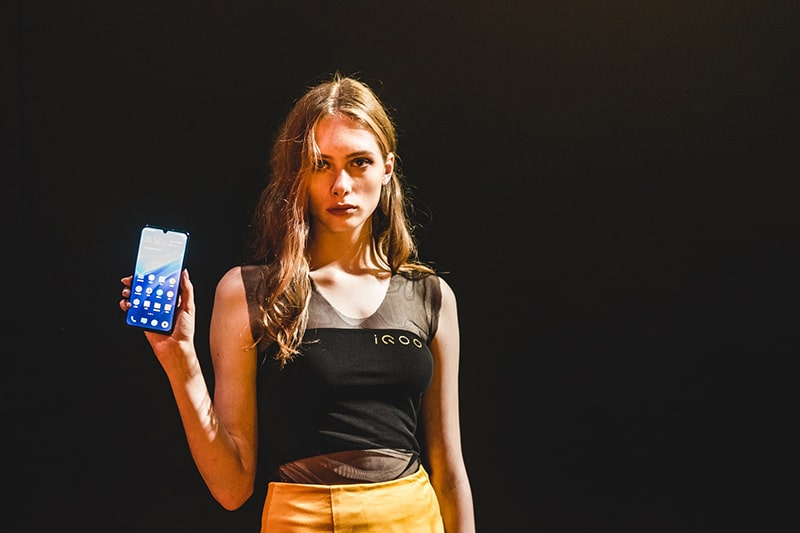 Eine ernsthafte Frau, die im Stehen ein Smartphone in der rechten Hand hält