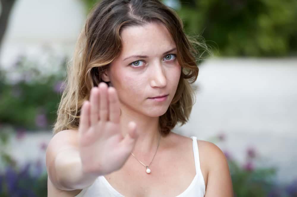 Eine ernsthafte Frau gestikuliert mit der Hand, das ist genug